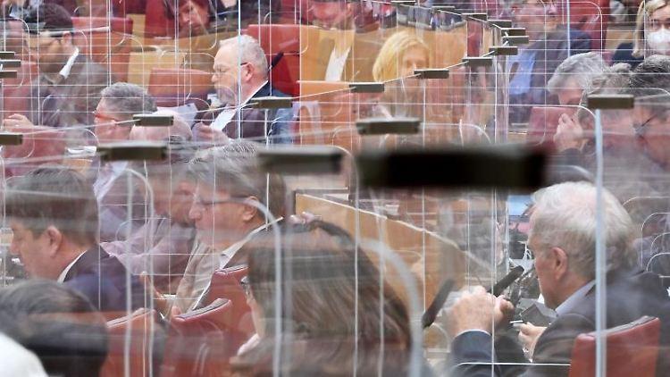 Abgeordnete des bayerischen Landtags sitzen im Plenarsaal hinter Plexiglasabtrennungen. Foto: Peter Kneffel/dpa