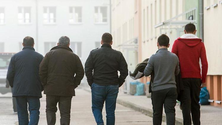 Asylbewerber gehen über das Gelände der Zentralen Ausländerbehörde in Eisenhüttenstadt. Foto: Patrick Pleul/dpa-Zentralbild/dpa/Archivbild
