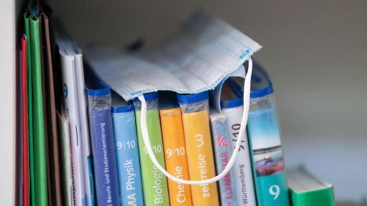 Ein Mund-Nasen-Schutz liegt in einem Klassenzimmer auf Schulbüchern. Foto: Marijan Murat/dpa/Symbolbild