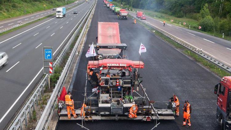 Bauarbeiter asphaltieren eine Autobahn. Foto: Julian Stratenschulte/dpa/Symbolbild