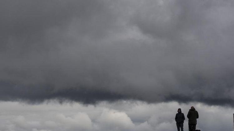 Dunkle Wolken ziehen über Spaziergänger hinweg, die mit dem Hund über einen Feldweg gehen. Foto: Boris Roessler/dpa/Symbolbild