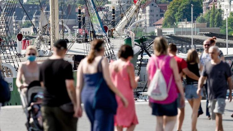 Touristen flanieren auf der Hochwasserschutzanlage am Baumwall. Foto: Markus Scholz/dpa/Archiv