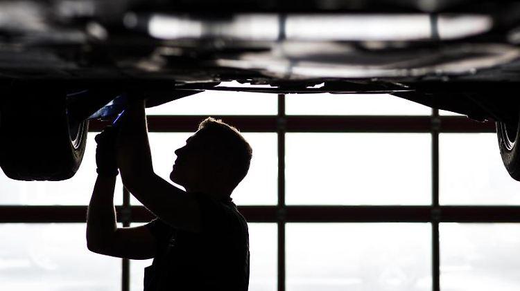 Ein Mechaniker arbeitet in einer KfZ-Werkstatt an der Unterseite eines Autos, das auf der Hebebühne steht. Foto: David-Wolfgang Ebener/dpa/Symbol