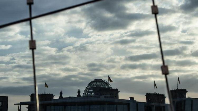 Der Reichstag spiegelt sich in der Glasfassade eines Bürogebäudes. Foto: Paul Zinken/dpa-Zentralbild/dpa