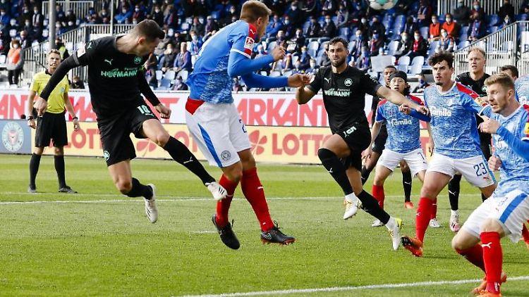 Fürths Branimir Hrgota (l) köpft gegen Kiels Hauke Wahl (2.v.l.) auf das Tor. Foto: Frank Molter/dpa