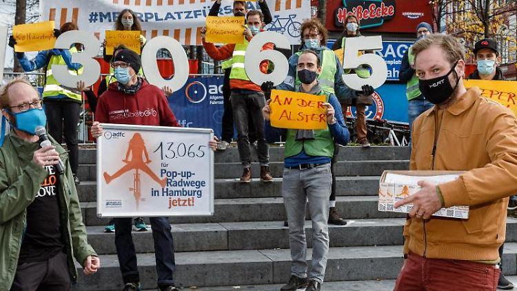 Verkehrssenator Anjes Tjarks hält einen Karton der Petition