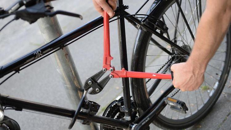 Ein Mann versucht ein Fahrradschloss aufzubrechen (gestellte Szene). Foto: Andreas Gebert/dpa/Illustration