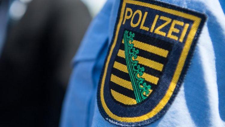 Das Logo der sächsischen Polizei ist an einem Polizeiuniform angebracht. Foto: Monika Skolimowska/ZB/dpa/Symbolbild
