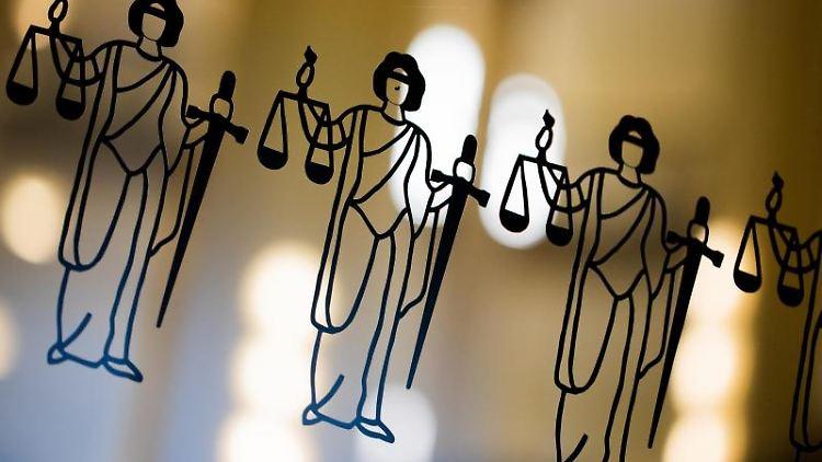 Die Justitia ist an einer Türscheibe angebracht. Foto: Rolf Vennenbernd/dpa/Symbol