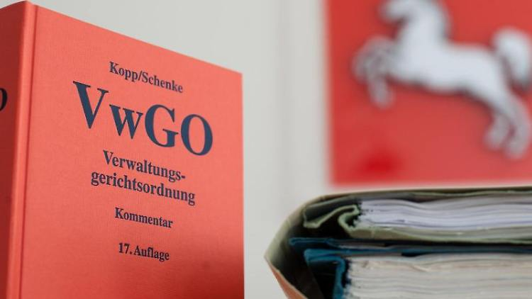 Die Verwaltungsgerichtsordnung steht neben Akten im Niedersächsischen Oberverwaltungsgericht (OVG) auf einem Tisch. Foto: Philipp Schulze/dpa/Illustration