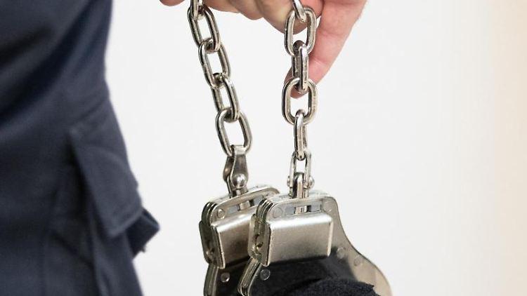 Ein Justizbeamter trägt Handschellen. Foto: Friso Gentsch/dpa/Symbolbild