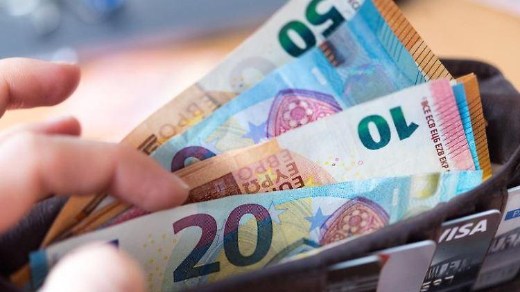 Eine Frau hält eine Geldbörse mit zahlreichen Banknoten in der Hand. Foto: Monika Skolimowska/zb/dpa/Symbolbild