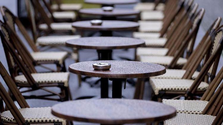 Leere und vom Regen nasse Tische eines Cafes. Foto: Christoph Soeder/dpa/Archiv