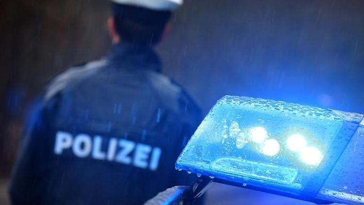 Ein Polizist steht im Regen vor einem Streifenwagen dessen Blaulicht aktiviert ist. Foto: Karl-Josef Hildenbrand/dpa/Archiv