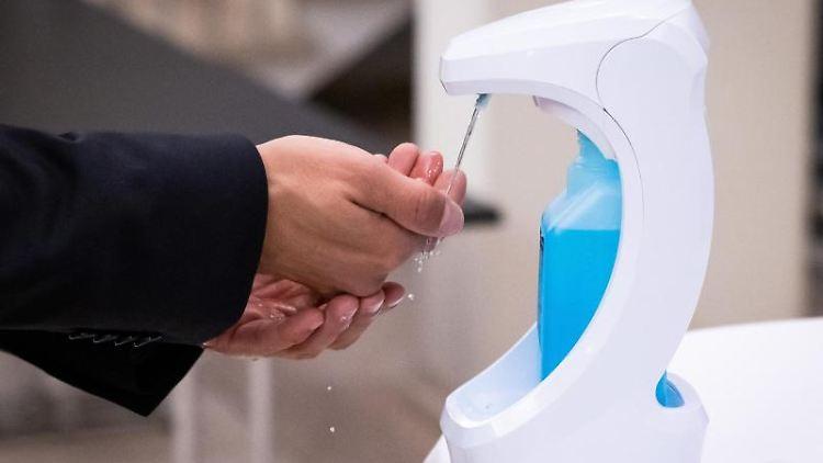Eine Person desinfiziert sich die Hände. Foto: Christian Charisius/dpa/Symbolbild