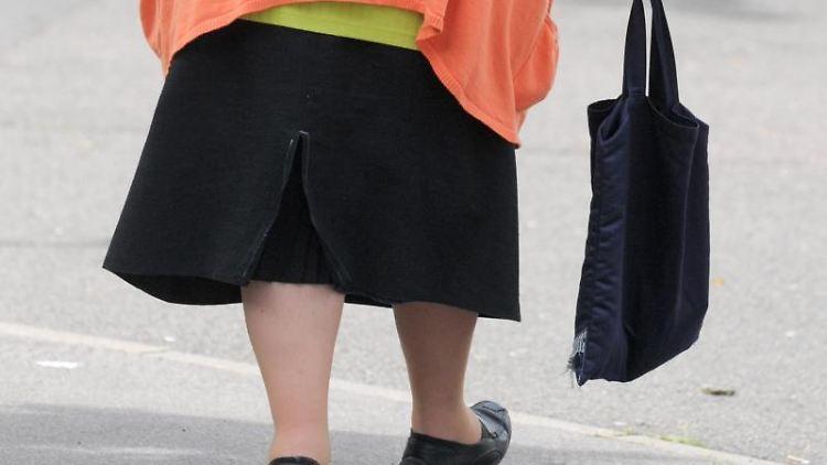 Eine übergewichtige Frau geht über den Bürgersteig. Foto: Peter Endig/dpa-Zentralbild/dpa/Archiv/Symbolbild