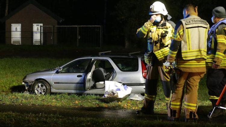 Einsatzkräfte stehen vor einem Unfallauto. Foto: David Young/dpa