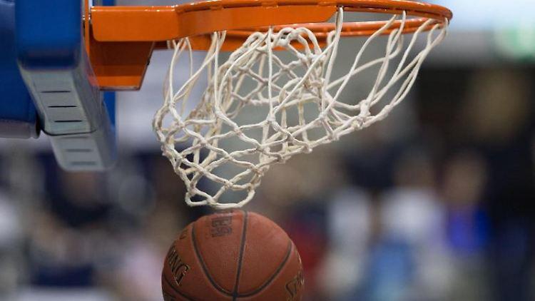 Ein Basketball fällt durch das Netz vom Basketballkorb. Foto: Lukas Schulze/dpa/Symbolbild