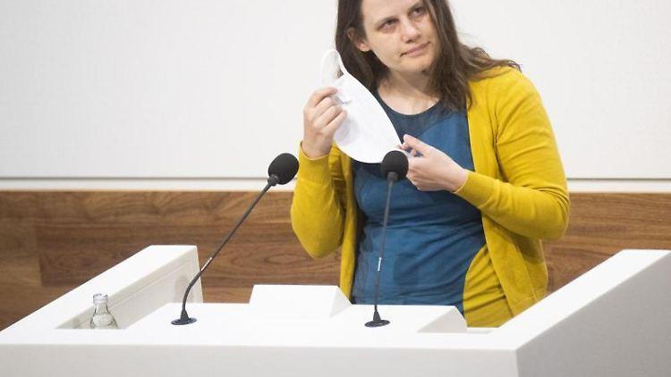 Julia Willie Hamburg nimmt am Rednerpult im Landtag ihren Mund-Nasen-Schutz ab. Foto: Julian Stratenschulte/dpa