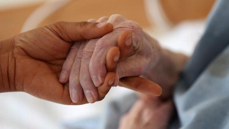 Eine Pflegerin hält im Altenheim die Hand einer Bewohnerin. Foto: Oliver Berg/dpa/Symbolbild