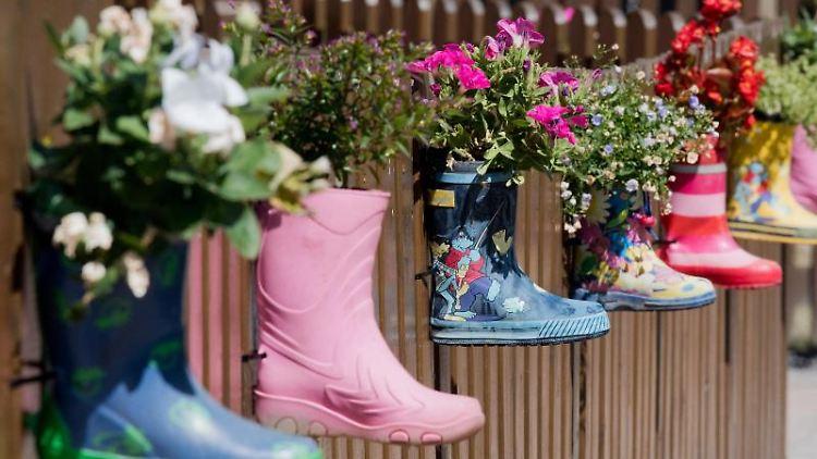 Gummistiefel mit Blumen hängen am Zaun eines Kindergartens. Foto: Julian Stratenschulte/dpa/Symbolbild