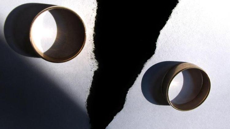 Zwei Eheringe liegen auf einem zerrissenen Papier. Foto: Karl-Josef Hildenbrand/dpa/Symbolbild