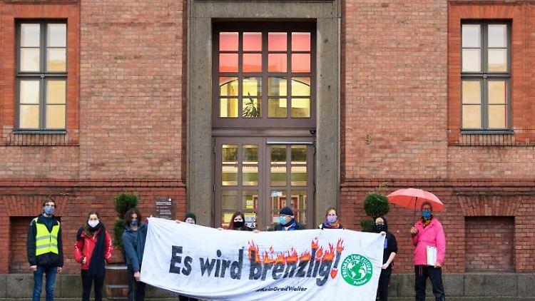 Demonstranten halten vor dem Gebäude der Sparkasse auf dem Luisenplatz ein Transparent