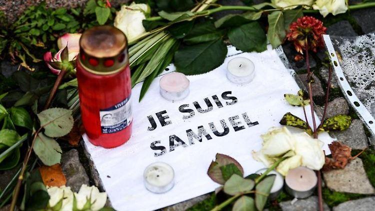 """Vor der französischen Botschaft liegen Blumen, Kerzen und ein Blatt mit Aufschrift """"Je suis Samuel"""". Foto: Kira Hofmann/dpa-Zentralbild/dpa/Archivbild"""