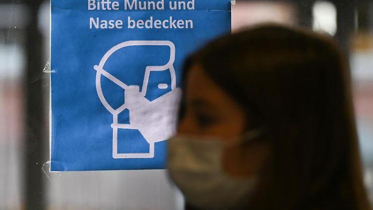 Eine Frau mit Mund-Nasen-Schutz geht an einem Plakat vorbei, das auf das Tragen einer Maske hinweist. Foto: Arne Dedert/dpa/Symbolbild