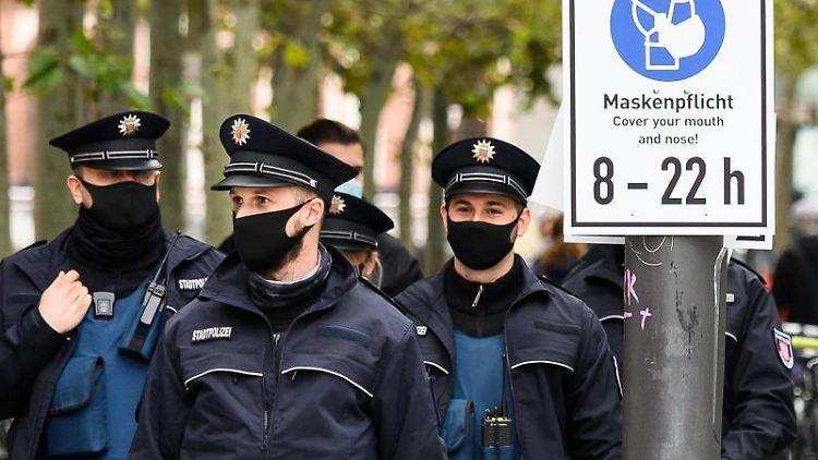 Polizisten kontrollieren die Einhaltung der Maskenpflicht auf einer Einkaufsstraße. Foto: Andreas Arnold/dpa/Archivbild
