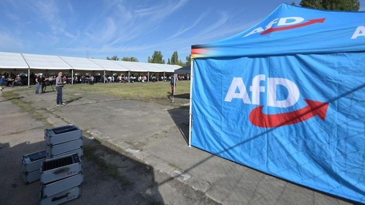 AfD-Mitglieder sitzen auf einem Landesparteitag der AfD in einem Zelt. Foto: Heiko Rebsch/dpa-Zentralbild/dpa/Archivbild
