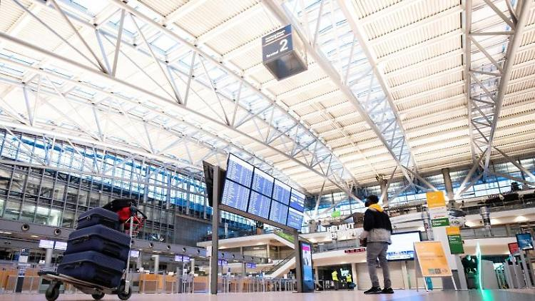 Ein Fluggast steht vor der Anzeigetafel in der Abflughalle im Terminal 2 am Flughafen Hamburg. Foto: Christian Charisius/dpa/Archivbild