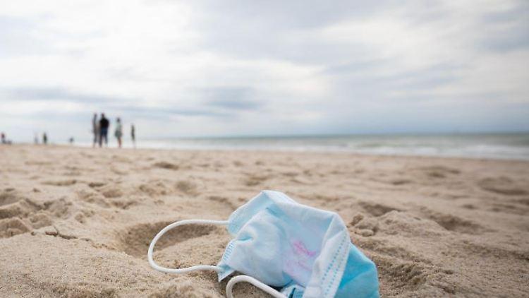 Ein gebrauchter Mundschutz mit Resten von Lippenstift am Strand von Westerland auf Sylt. Foto: Christian Charisius/dpa/Archivbild