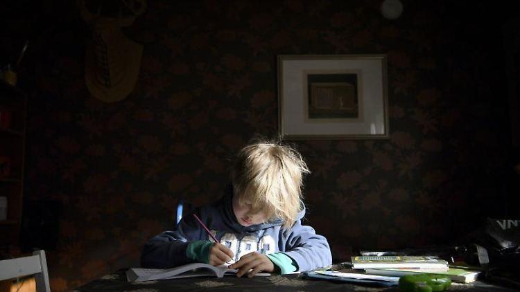 Ein Junge sitzt zu Hause an einem Tisch und schreibt in einem Schulheft. Foto: Antti Aimo-Koivisto/Lehtikuva/dpa/Symbolbild