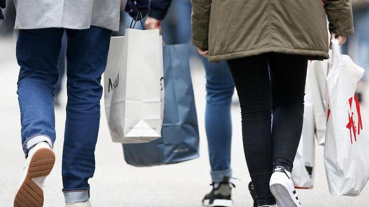 Passanten gehen mit Einkaufstüten durch eine Innenstadt. Foto: picture alliance / Bodo Marks/dpa/Archivbild
