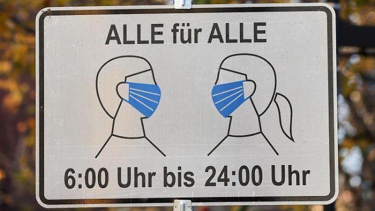 Ein Schild weist auf eine Maskenpflicht von 06:00 bis 24:00 Uhr hin. Foto: Jan Woitas/dpa-Zentralbild/dpa/Archivbild