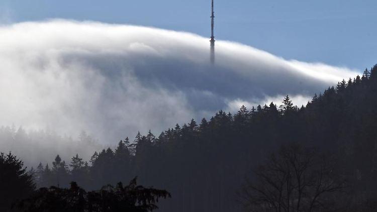 Ein Sendemast ragt an einem Hügel aus dem Nebel. Foto: Martin Schutt/dpa-Zentralbild/dpa/Symbolbild
