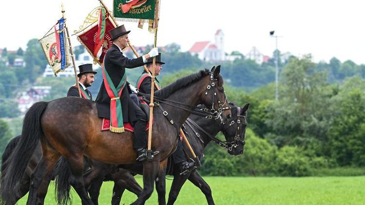 Standartenträger und Reiter aus Grünkraut reiten beim traditionellen