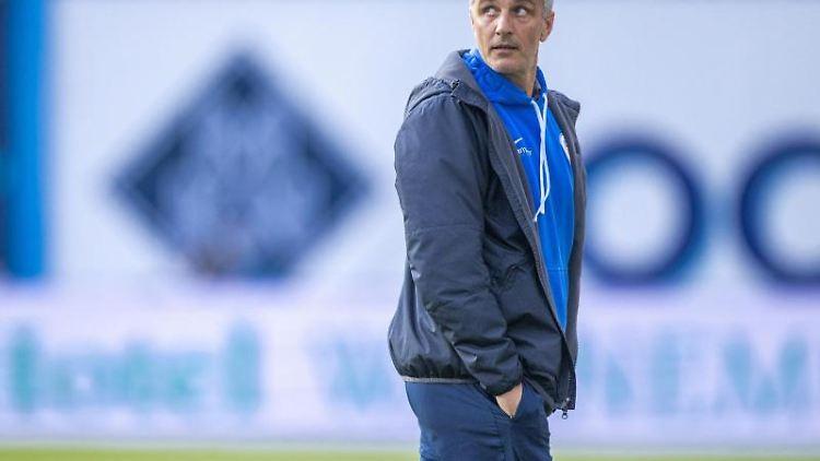 Rostocks Trainer Jens Härtel geht über den Rasen. Foto: Jens Büttner/dpa-Zentralbild/ZB/Archivbild