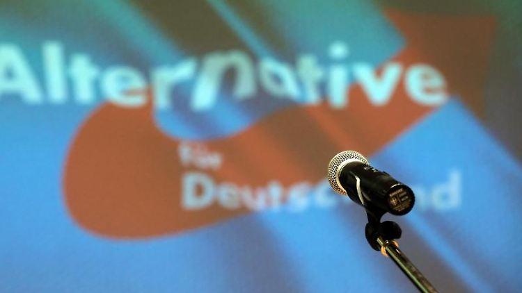 Ein Mikrofon steht bei einem AfD-Landesparteitag vor dem Partei-Logo. Foto: Sebastian Willnow/zb/dpa/Archivbild
