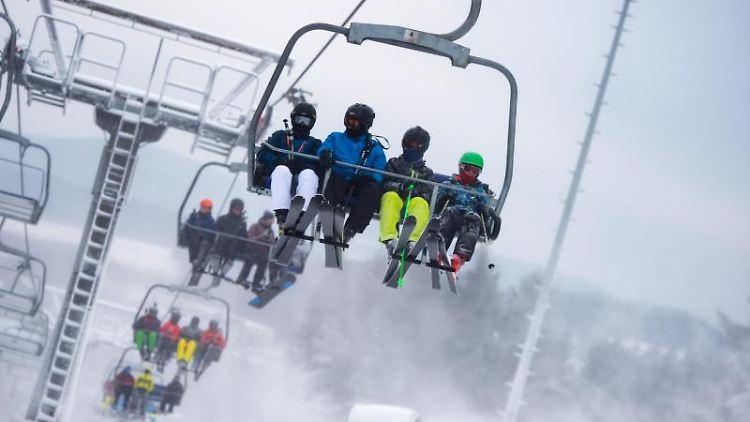 Skifahrer sitzen auf einem Sessellift im Skigebiet Winterberg. Foto: Christophe Gateau/dpa/Archivbild