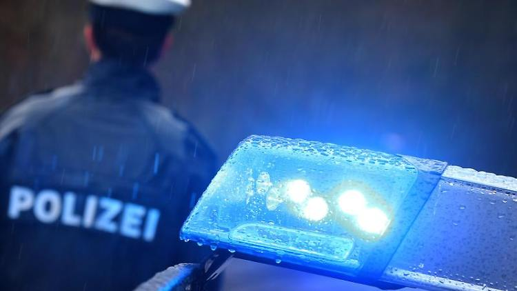 Ein Polizist vor einem Streifenwagen mit Blaulicht. Foto: Karl-Josef Hildenbrand/dpa/Symbolbild