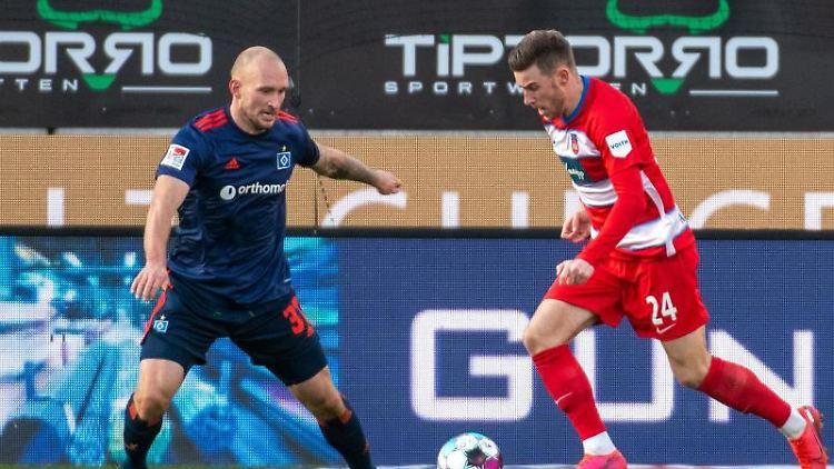 Heidenheims Christian Kühlwetter (r) und Hamburgs Toni Leistner kämpfen um den Ball. Foto: Stefan Puchner/dpa