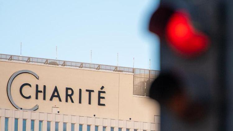Vor dem Hauptgebäude der Charité leuchtet eine rote Ampel. Foto: Christophe Gateau/dpa/Aktuell