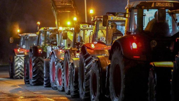 Landwirte blockieren mit ihren Traktoren die Zufahrt zu einem Lagerhaus der Rewe-Gruppe. Foto: Axel Heimken/dpa/Archivbild