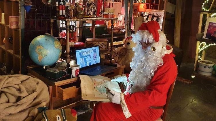 Ein Mann in einem Weihnachtsmann-Kostüm sitzt mit Smartphone und Tablet an einem kleinen Schreibtisch. Foto: Merle Roza/dpa/Archivbild