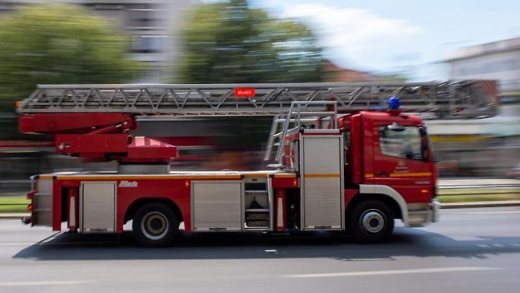Ein Feuerwehrauto fährt mit Blaulicht zu einem Einsatz. Foto: Monika Skolimowska/dpa-Zentralbild/dpa/Symbolbild