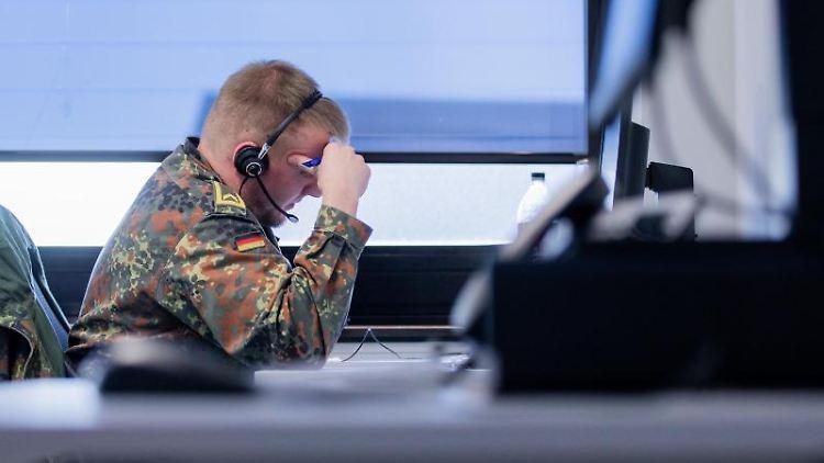 Ein Soldat der Bundeswehr telefoniert bei der Kontaktnachverfolung im Gesundheitsamt Grevenbroich. Foto: Rolf Vennenbernd/dpa/Archivbild