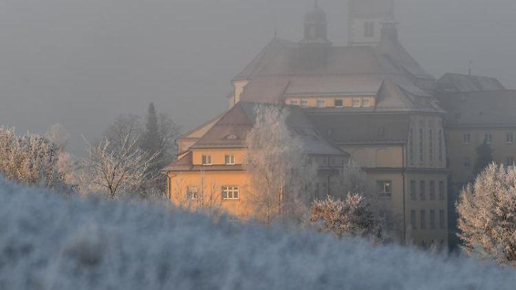Die Morgensonne strahlt in Reute nahe Bad Waldsee das Franziskanerinnen-Kloster an, während Wiese und Bäume frostbedeckt sind. Foto: Felix Kästle/dpa/Archivbild