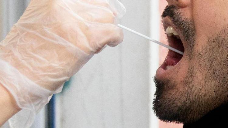 Ein Patient lässt vor einer Arztpraxis einen Abstrich machen. Foto: Kay Nietfeld/dpa/Symbolbild